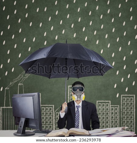Male entrepreneur working in office while holding an umbrellas and wearing a gas mask - stock photo