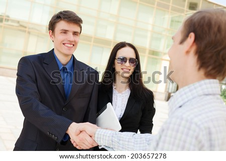 Male entrepreneurs greeting each other with businesswoman near by - stock photo