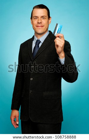 Male executive showing credit card to camera against gradient background - stock photo