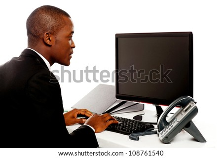 Male executive typing and looking at lcd screen working in office