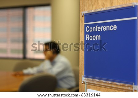 Male executive using phone in conference room