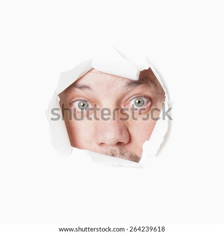 male eyes staring through torn hole voyeurism or stalking concept                              - stock photo