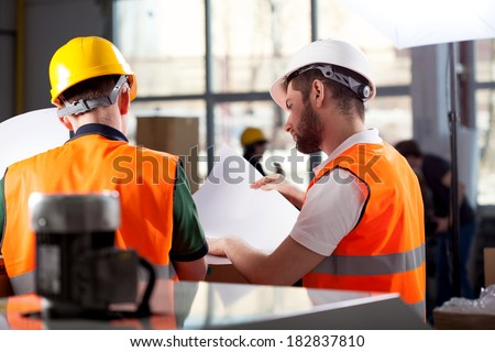 Male factory worker and supervisor are analyzing plans - stock photo