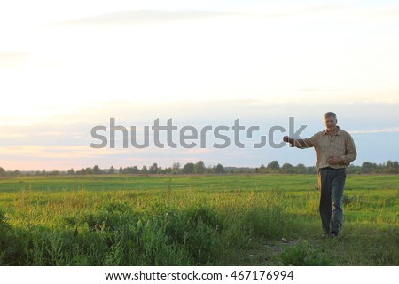 Male farmer checks his fields with crops