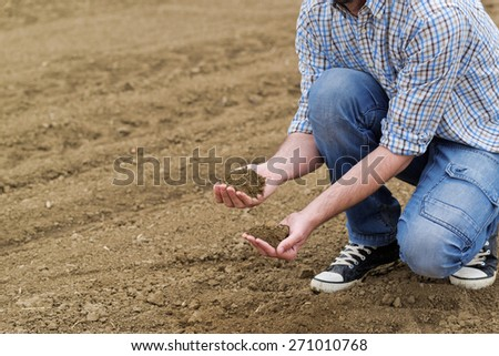 Male Farmer Examines Soil Quality on Fertile Agricultural Farm Land, Agronomist Checking Soil in Hands. - stock photo