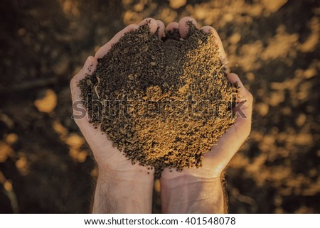 Male farmer holding pile of soil and examining its quality on fertile agricultural land, agronomist preparing land for new crop raising season, close up of hands. - stock photo