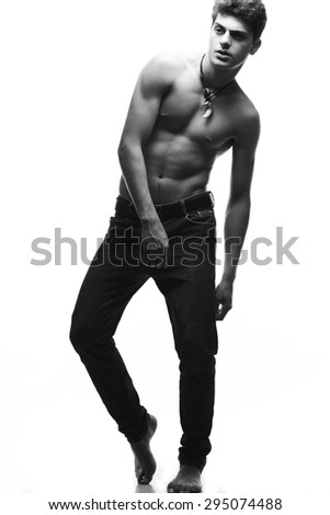 Male fashion concept. Fashionable young man with haircut wearing trendy jeans & posing over white background. Perfect hair & skin. Leather accessories. Street style. Full length portrait. Studio shot