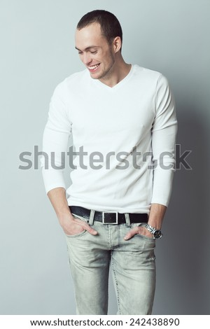 Male fashion concept. Fashionable young man with short haircut wearing trendy clothes & posing over gray background. Perfect smile & skin. Hands in pockets. Street style. Studio shot - stock photo