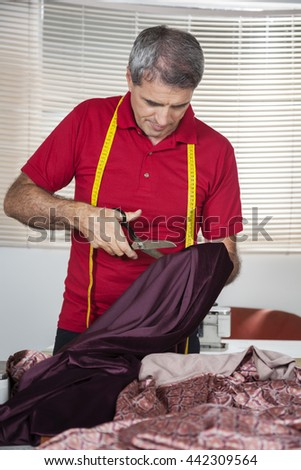 Male Fashion Designer Cutting Textile In Factory