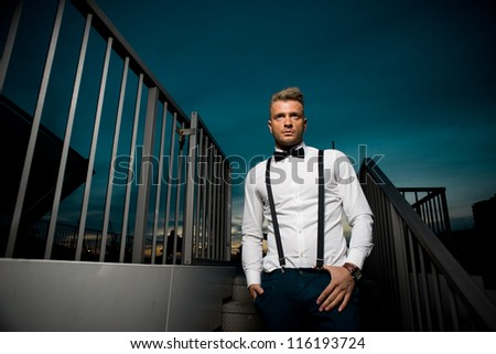 Male fashion model posing in twilight hour in the city