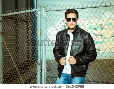 Male fashion model wearing leather jacket and jeans in a rustic setting.  - stock photo