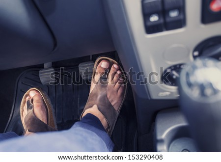 Male feet on the pedals of a car - stock photo