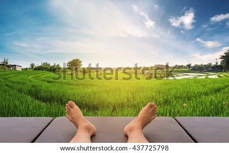Male feet relaxing on leather bed at rice field in countryside area in sunrise morning  - stock photo