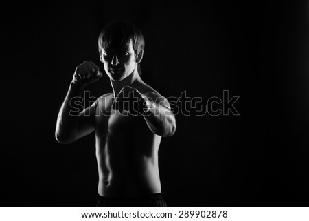 Male fighter kung fu doing kata. Low key. Dramatic portrait. Space for text. Healthy lifestyle concept. - stock photo