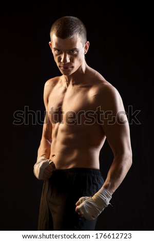 Male Fighter posing on black background.