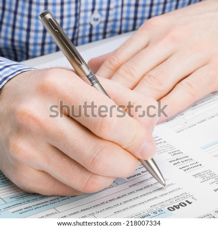 Male filling out 1040 United States of America Tax Form - studio shot - 1 to 1 ratio - stock photo