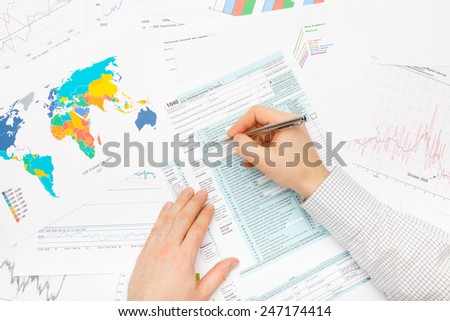 Male filling out 1040 US Tax Form - stock photo