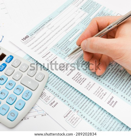 Male filling out US 1040 Tax Form - close up shot - stock photo