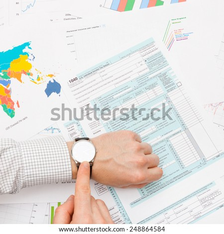Male filling out 1040 US Tax Form - tax time - studio shot - stock photo