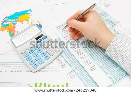 Male filling out 1040 US Tax Form using silver ball pen - stock photo
