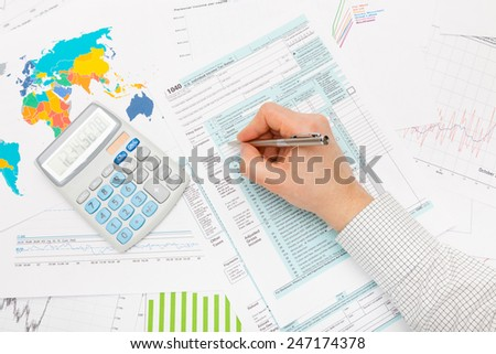 Male filling out 1040 US Tax Form with lots of financial documents around - stock photo