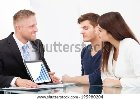Male financial advisor showing investment plans to couple on laptop at office desk - stock photo