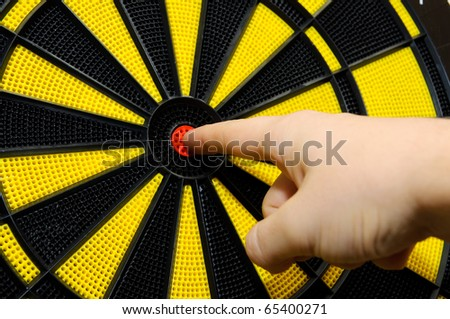 Male finger showing bulls eye on dart board game - stock photo
