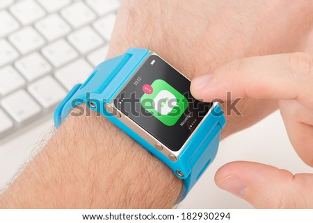 Male finger taps messenger icon on blue smart watch - stock photo