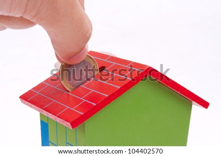 Male fingers put one-euro coin in the house-shape bank - stock photo