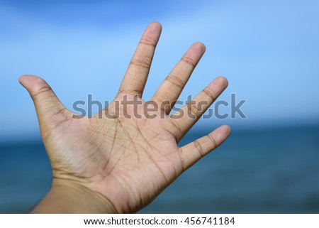 Male fingers showing number 5 isolated on bokeh blue-sea background. Copyspace is available.