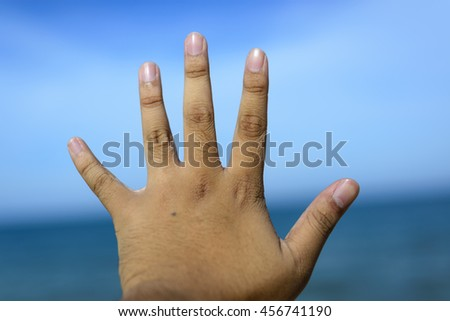 Male fingers showing number 5 isolated on bokeh blue-sea background. Copyspace is available. - stock photo
