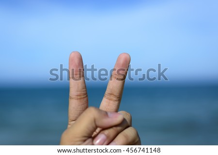 Male fingers showing number 2 or peace sign isolated on bokeh blue-sea background. Copyspace is available. - stock photo