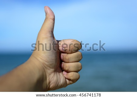 Male fingers showing thumbs up isolated on bokeh blue-sea background. Copyspace is available. - stock photo
