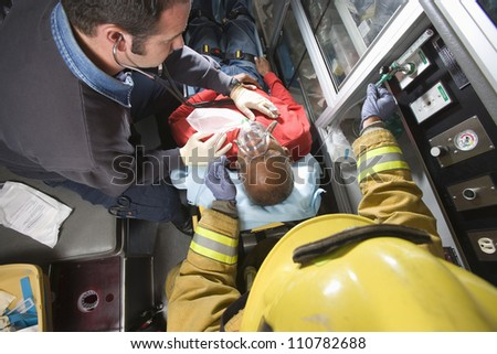 Male firefighter and EMT doctor taking care of an injured middle aged man in ambulance