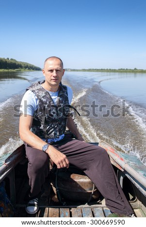 male fisherman on boat moves in river