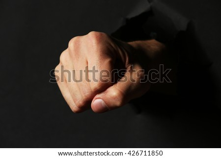 Male fist punching through black paper