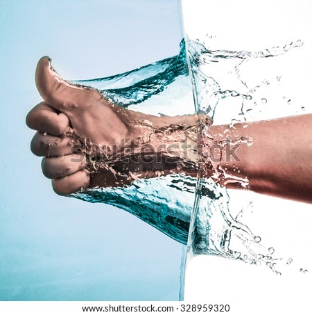 Male Fist through the Blue Water and splashing drops,Like hand sign
