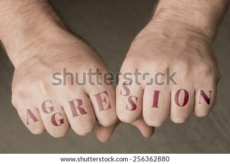 "Male fist with the word ""aggression"" - stock photo"