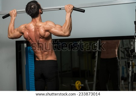 Male Fitness Athlete Doing Heavy Weight Exercise For Back - stock photo
