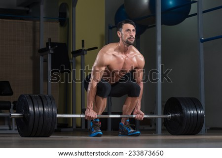 Male Fitness Athlete Lifting Deadlift In The Gym - stock photo