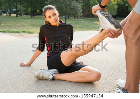 Male Fitness Instructor Straightening Woman's Leg  - stock photo