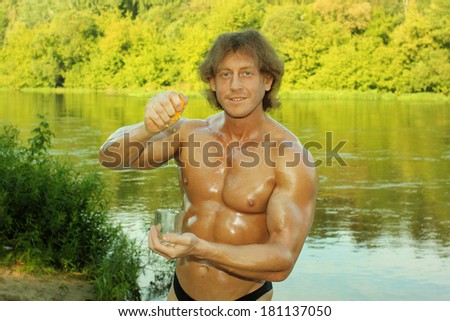 male fitness model bodybuilder squeezes out orange juice in a glass