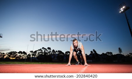Male fitness model training for sprinting on an athletic track - stock photo