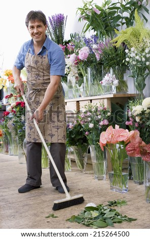 Male florist in apron standing in flower shop, sweeping floor with broom, smiling, portrait - stock photo