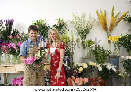 Male florist serving woman in flower shop, holding bunch of flowers, smiling, display in background