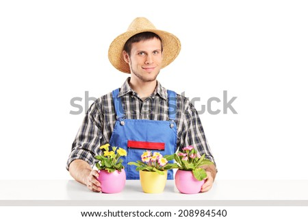 Male florist sitting on a table with many flower pots isolated on white background - stock photo