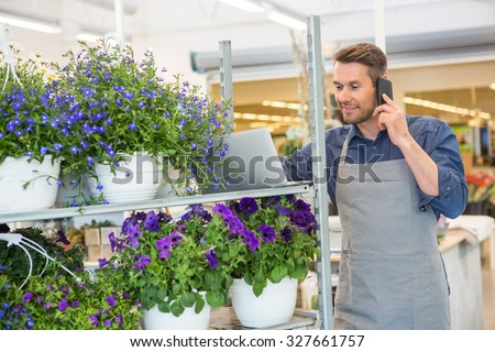 Male florist using mobile phone and laptop in flower shop