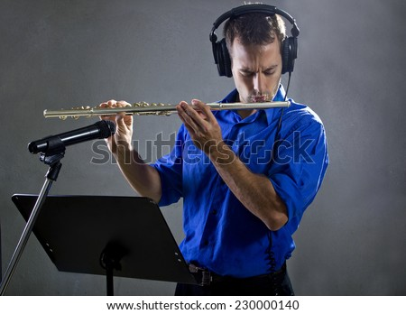 male flute player in a recording studio with headphones - stock photo