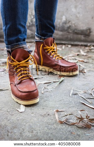 Male foot with brown leather shoes and jeans - stock photo