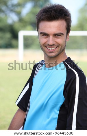 Male footballer in front of goal - stock photo